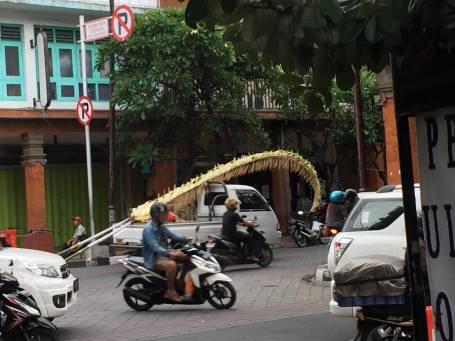 Sebuah kendaraan kecil, mengangkut penjor ke tempat tujuan (Foto Darma Putra)
